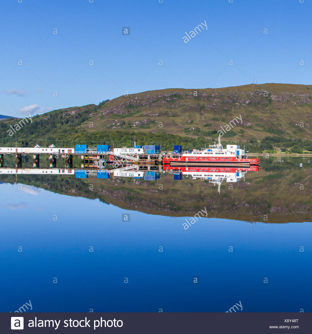 UK, Scotland, View of harbor and hill reflecting in water Stock Photo