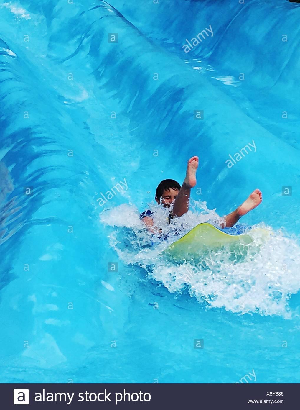 Boy On Water Slide - Stock Image