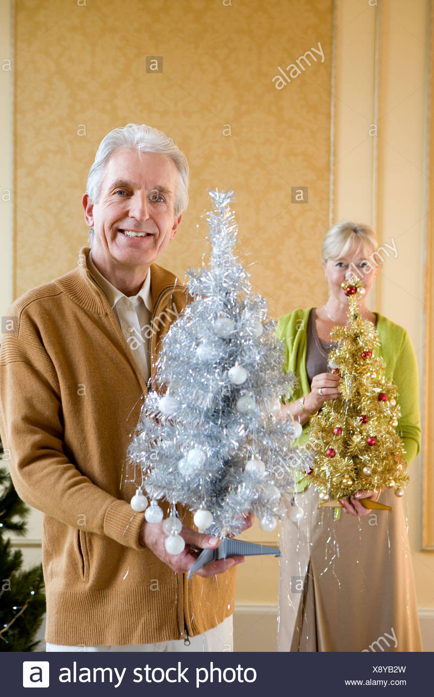 Senior couple with ornamental Christmas trees, smiling, portrait, close-up of man Stock Photo