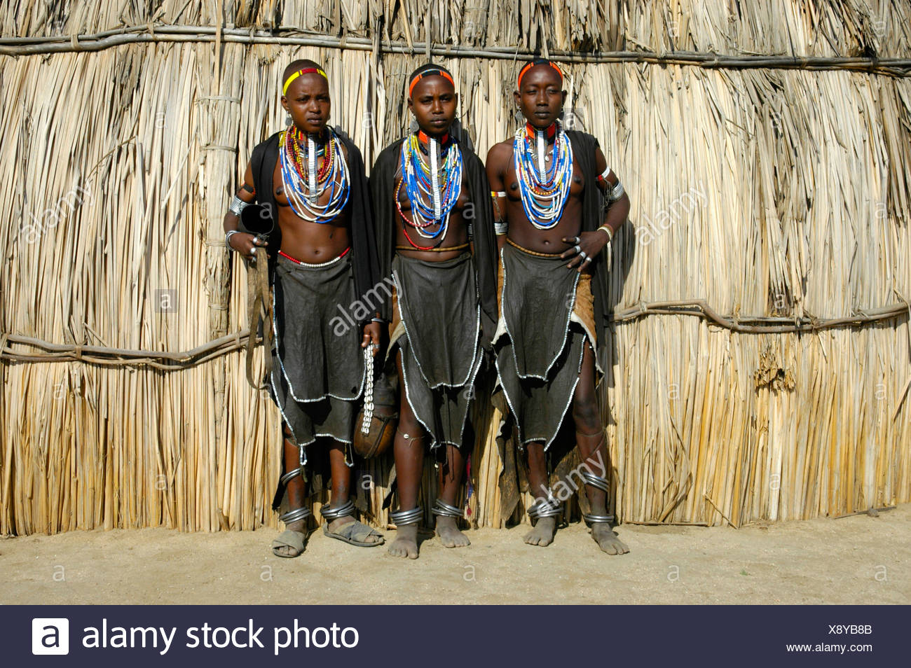 Three young women wearing leather skirts and lots of necklaces in front of straw hut, Erbore people, Weyto, Ethiopia, Africa - Stock Image