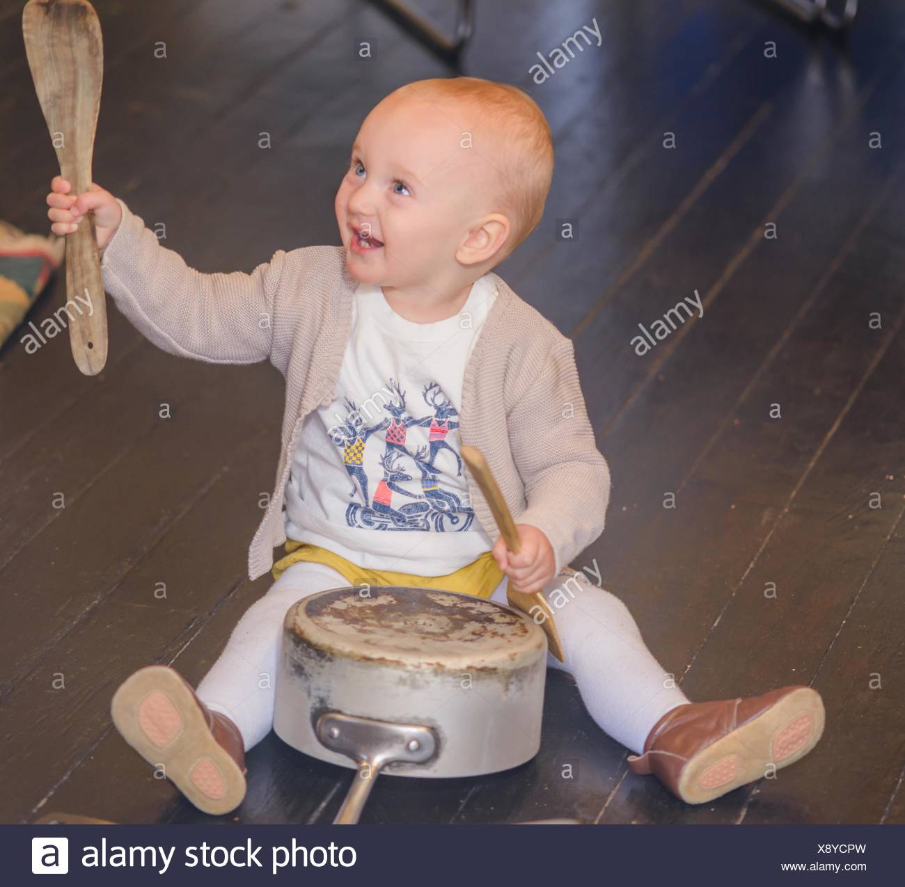 Toddler banging saucepan with kitchen utensils - Stock Image