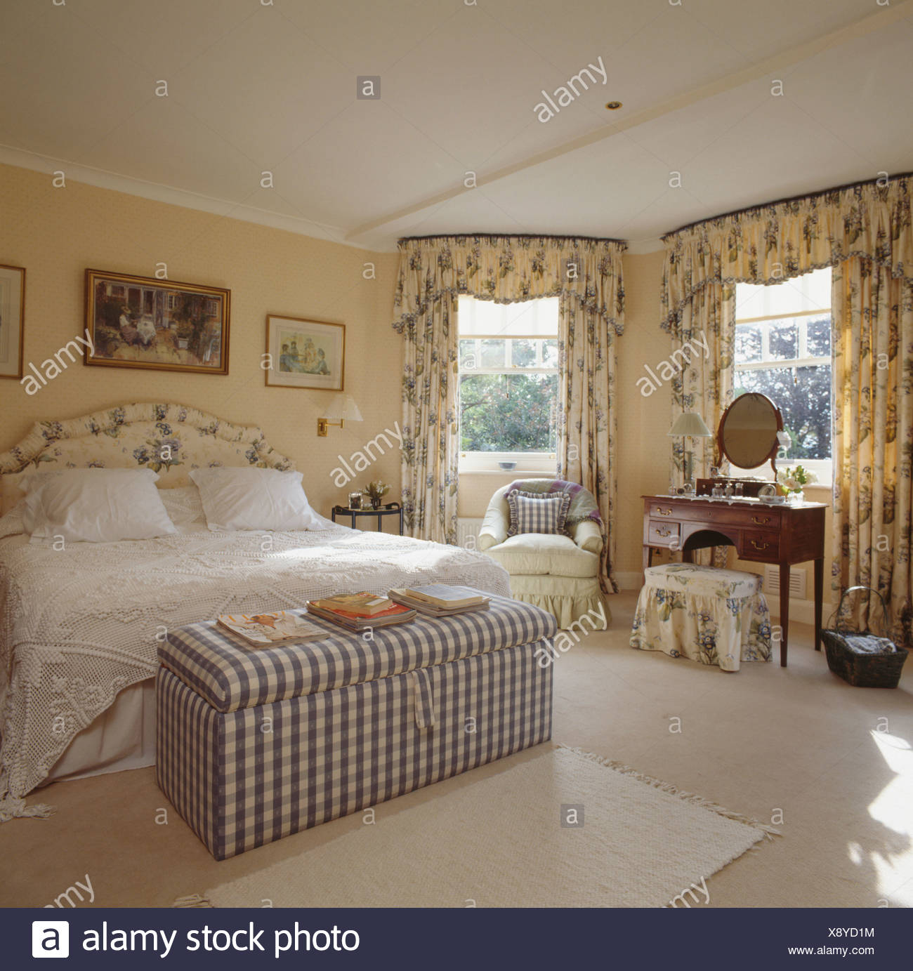 Checked Upholstered Ottoman In Pastel Yellow Bedroom With Patterned Yellow Floral Curtains And White Bedlinen Stock Photo Alamy