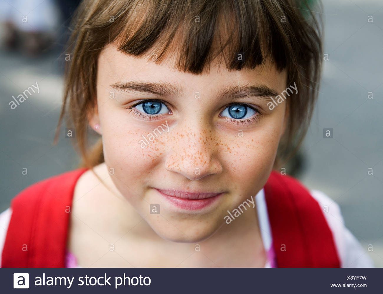 Portrait of a girl with big blue eyes and freckles, Sweden. - Stock Image