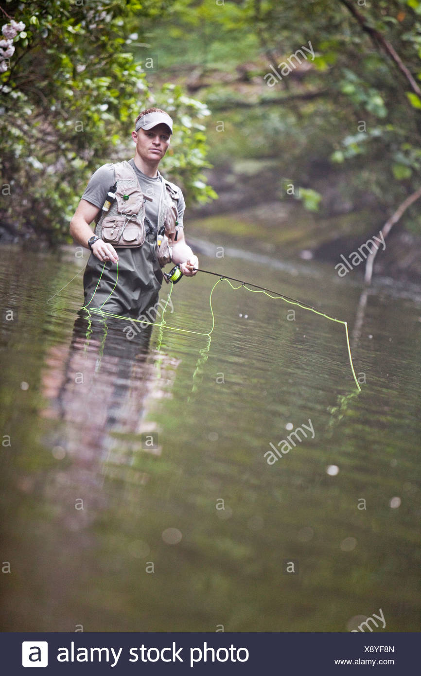 Close up of a man standing in still water fly fishing. - Stock Image