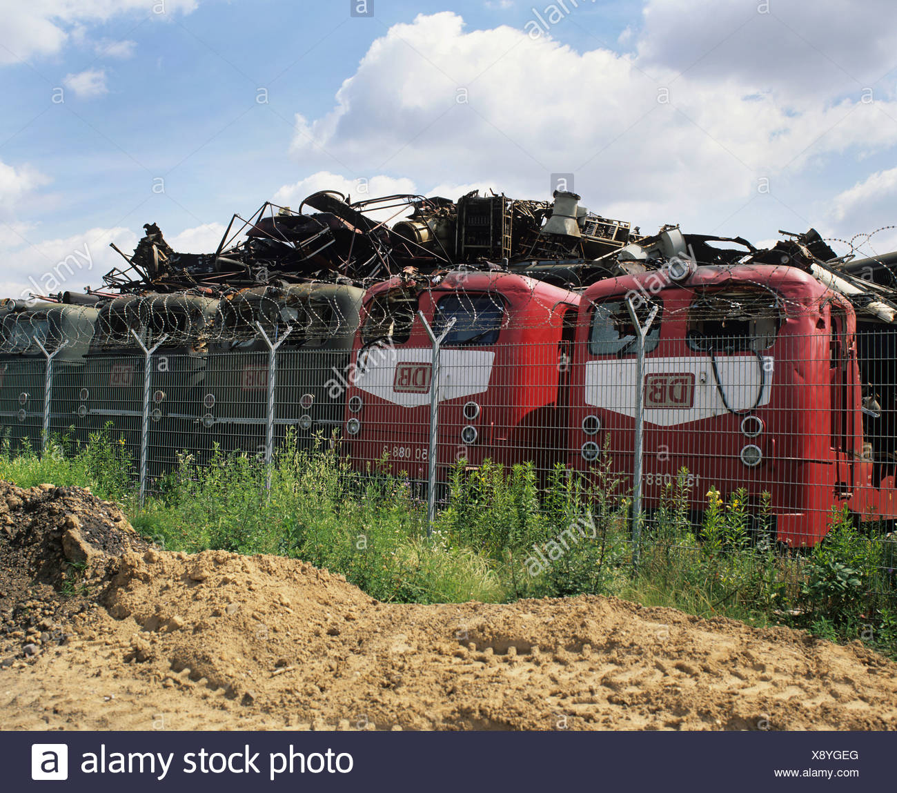 Scrapyard, electric trains and behind them piled-up old metal parts - Stock Image