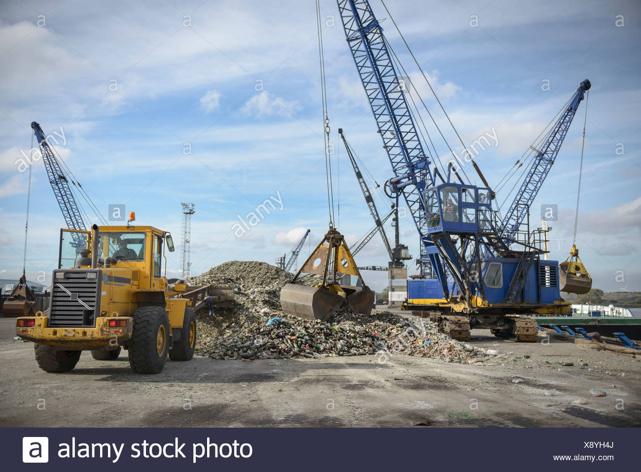 Crane and digger loading recycled glass onto ships - Stock Image