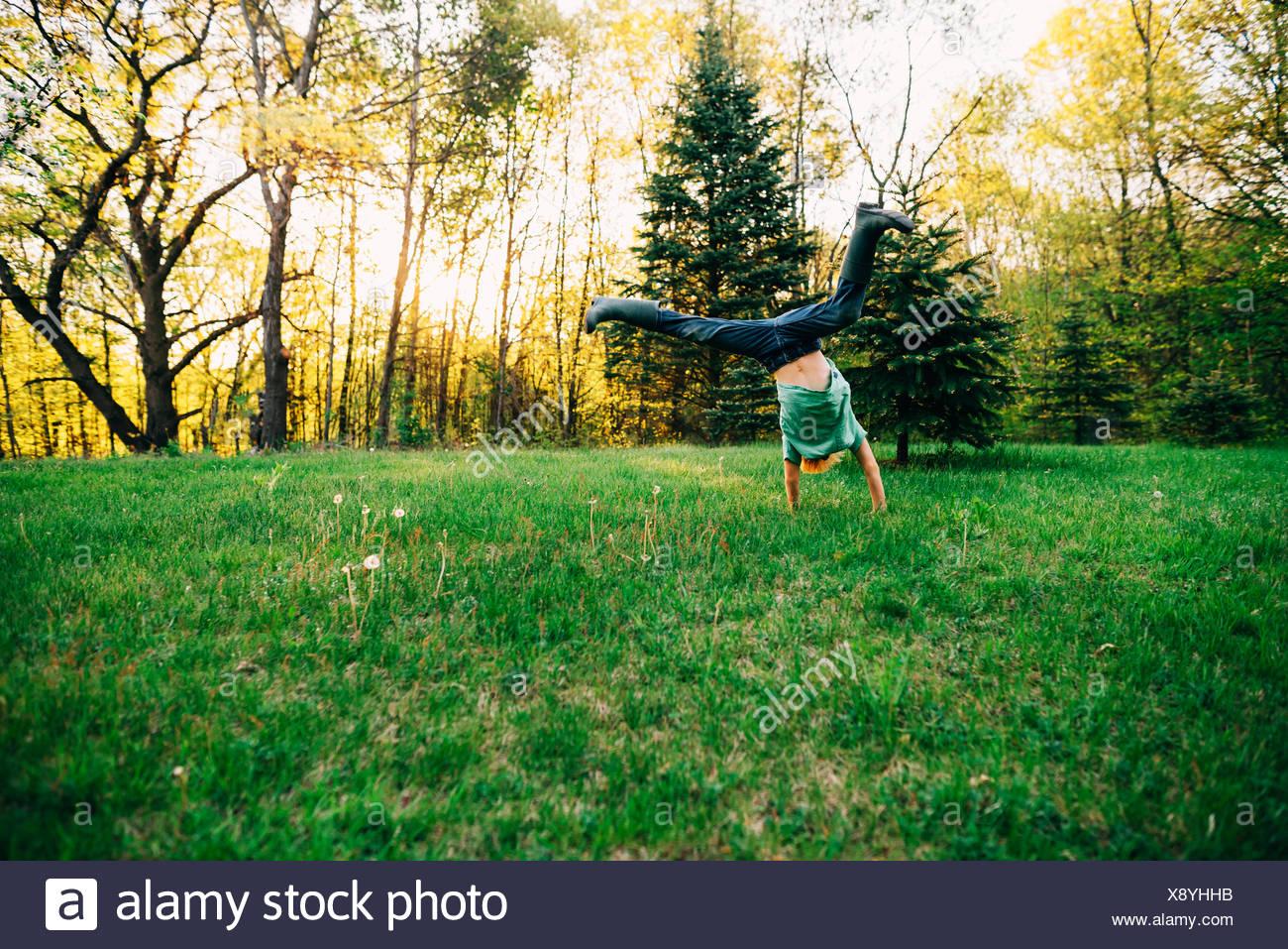 Boy doing a cartwheel in the garden - Stock Image