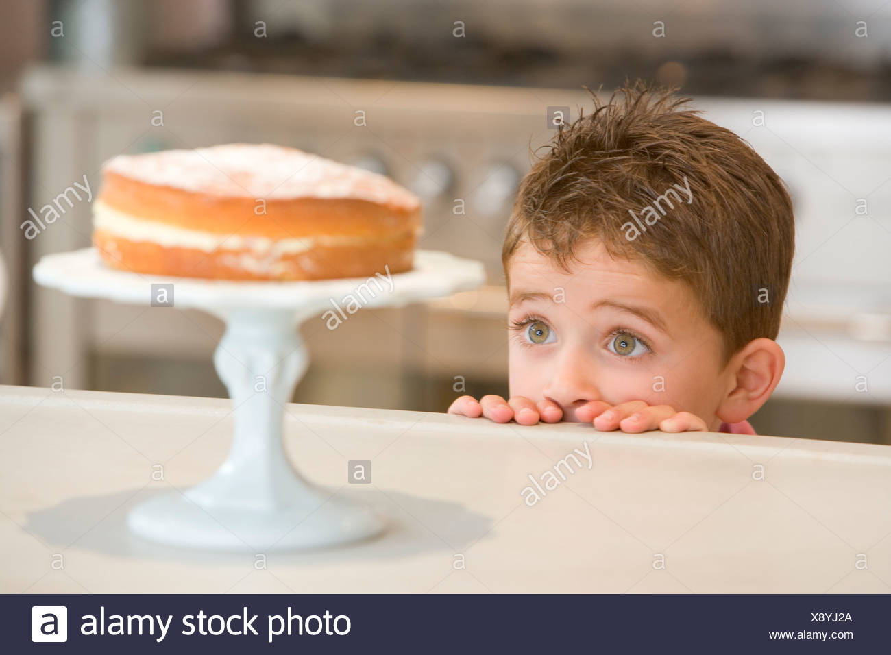 Young boy in kitchen looking at cake on counter Stock Photo