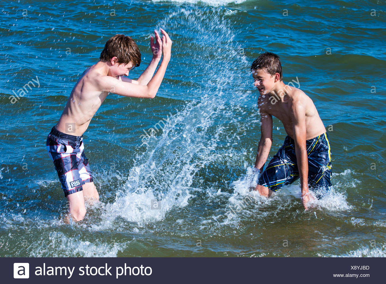 Two boys splashing water at each other in the ocean - Stock Image