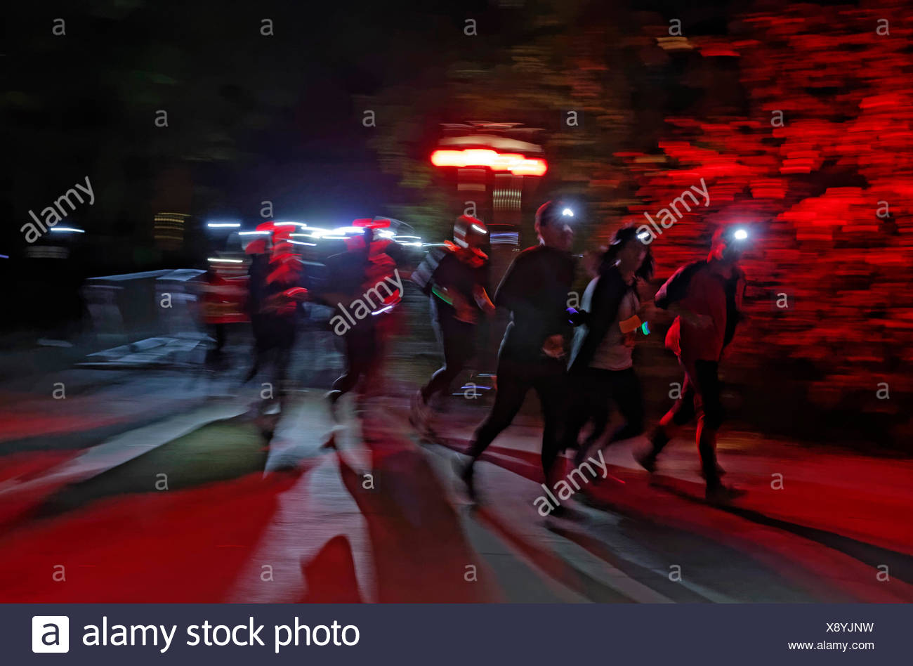 Runners wearing headlamps during a night run, Landschaftspark Duisburg-Nord, landscape park at a disused industrial steel works - Stock Image