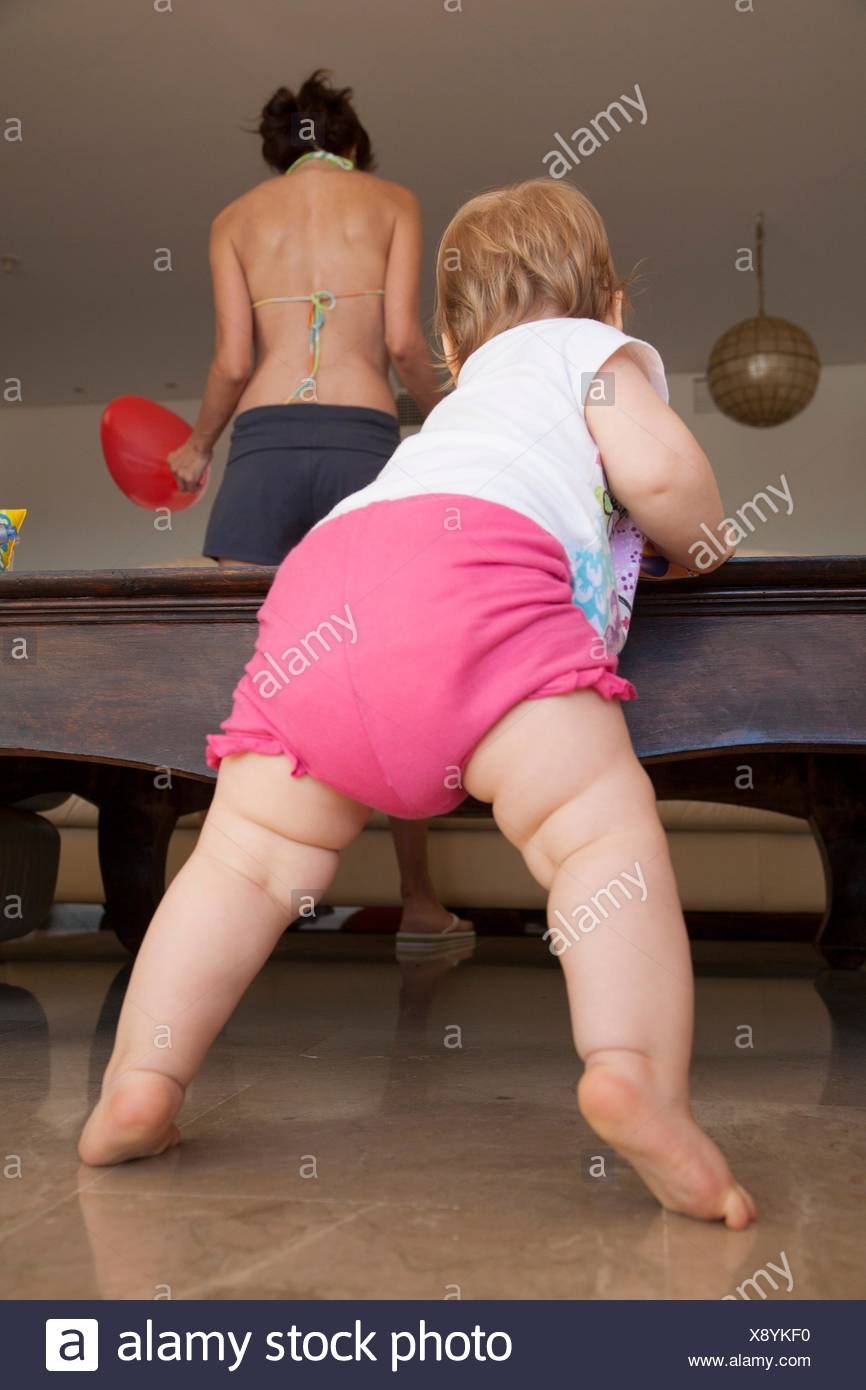 back of baby stand up clutching the table and mother. - Stock Image