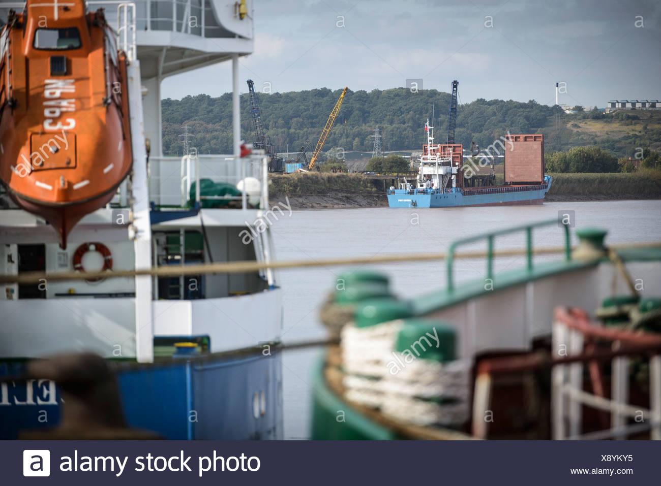 Small bulk load ship on river, view from port - Stock Image