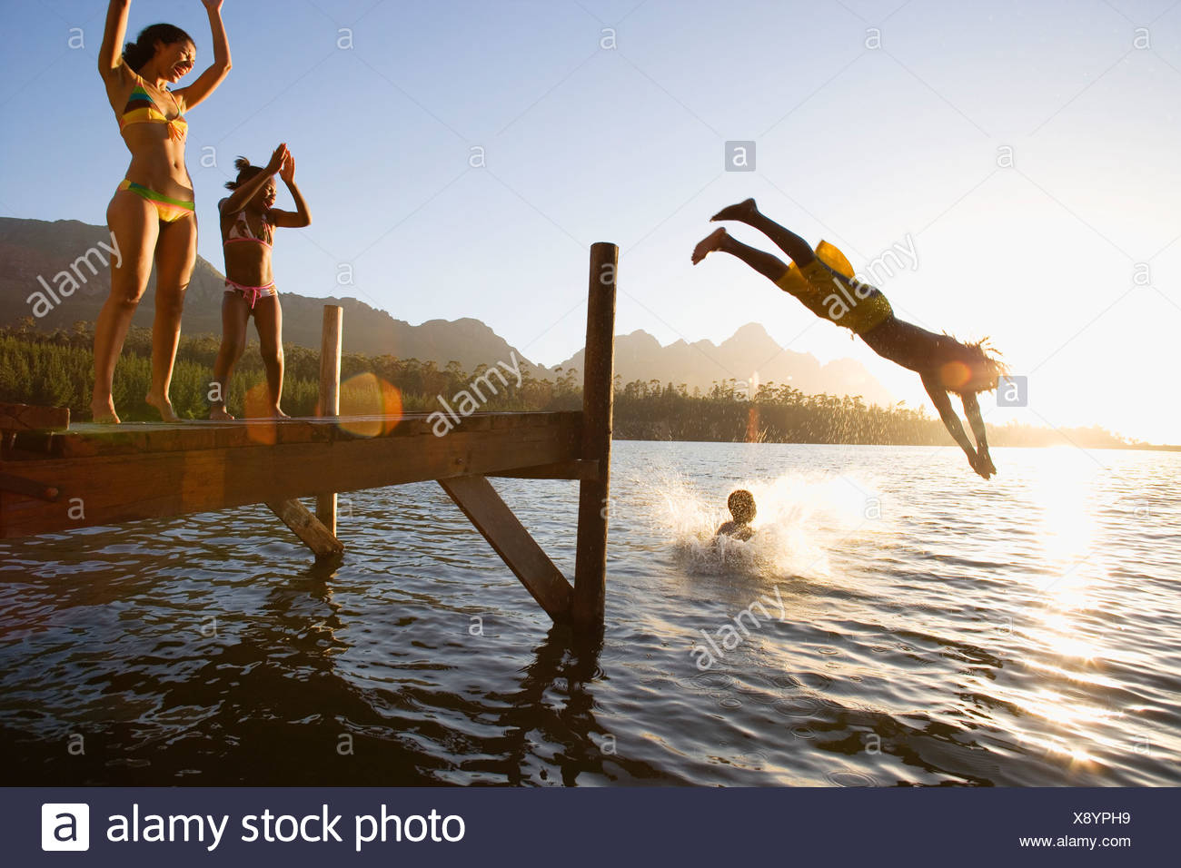 Father and son 8 10 in swimwear diving off jetty into lake at sunset mother and daughter 7 9 cheering lens flare - Stock Image