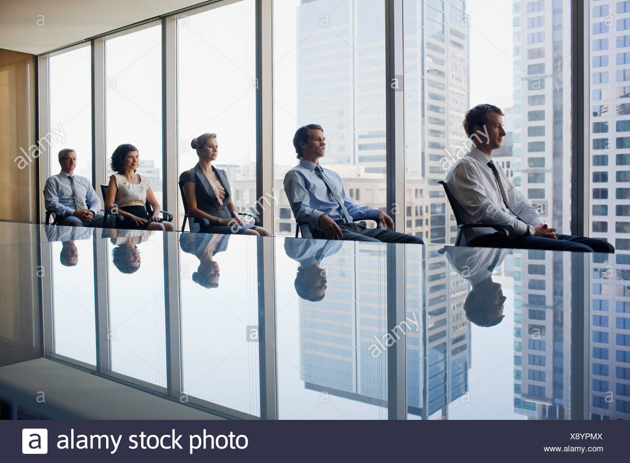 Business people sitting in row together in conference room - Stock Image