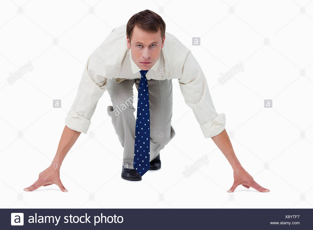 Businessman in sprinters position - Stock Image