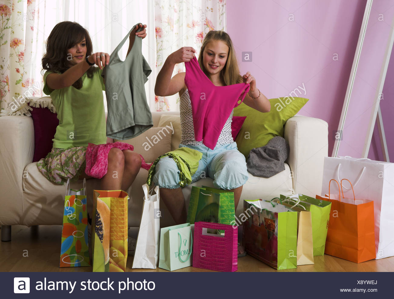 girl  sofa  purchase-bags  sit squeals  garments  views  cheerfully  series  people  teenagers  friends  two  friendship  bags - Stock Image