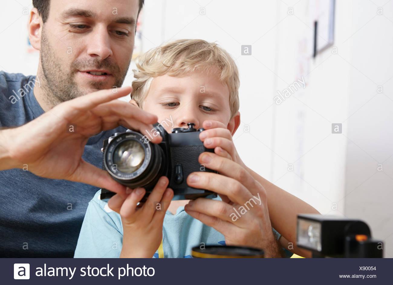 Father explaining analogue camera to son - Stock Image