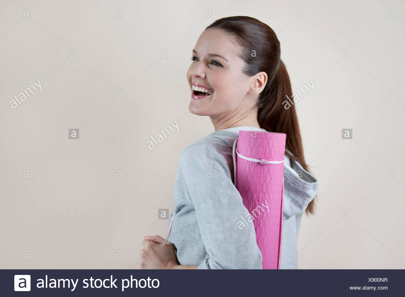 A young woman carrying a yoga mat, laughing Stock Photo