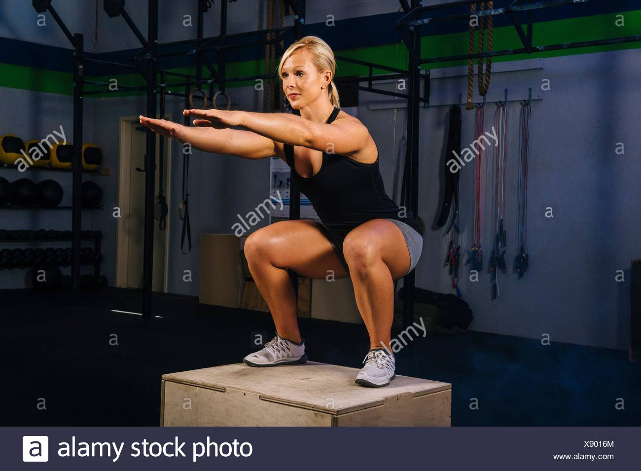Young woman squatting on gym box with arms reaching out - Stock Image