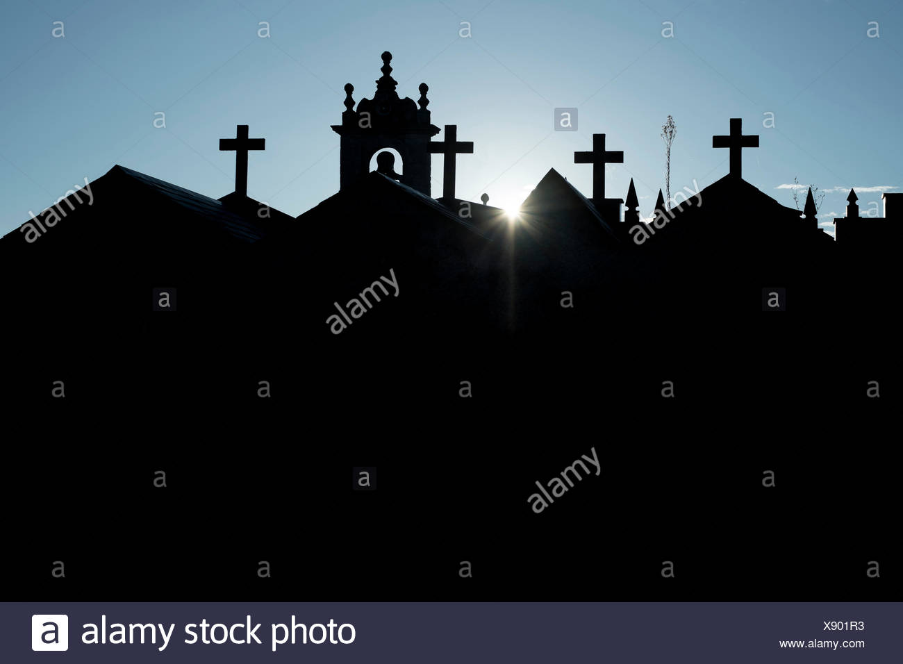 The sun peaks over a church and graveyard in Galicia, Spain on the Camino Primitivo, one route of the Camino de Santiago. - Stock Image