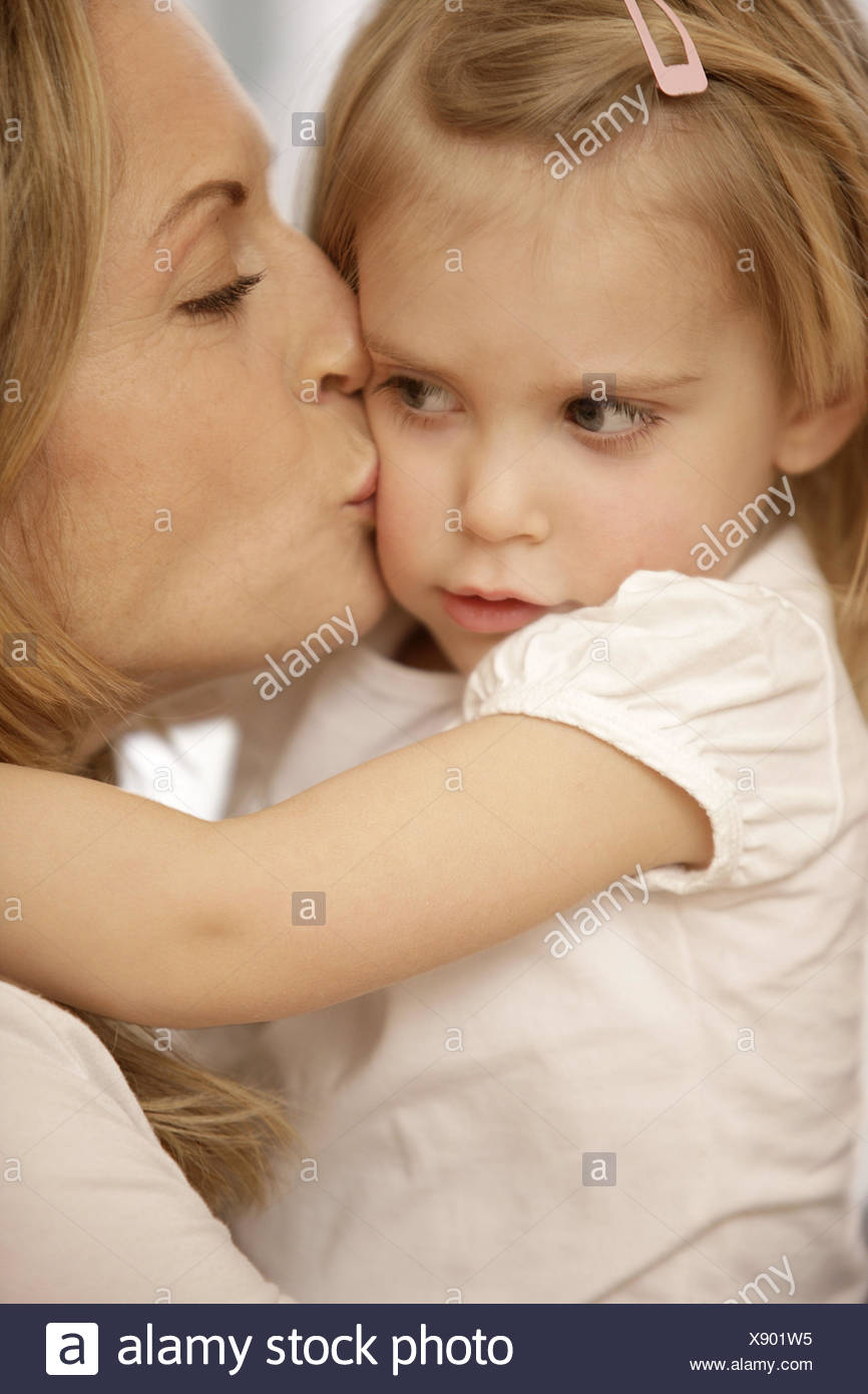 Nut, subsidiary, embrace, comfort, model released, people, woman, child, girl, blond, side view, suture, affection, kiss, motherly love, portrait, curled, - Stock Image