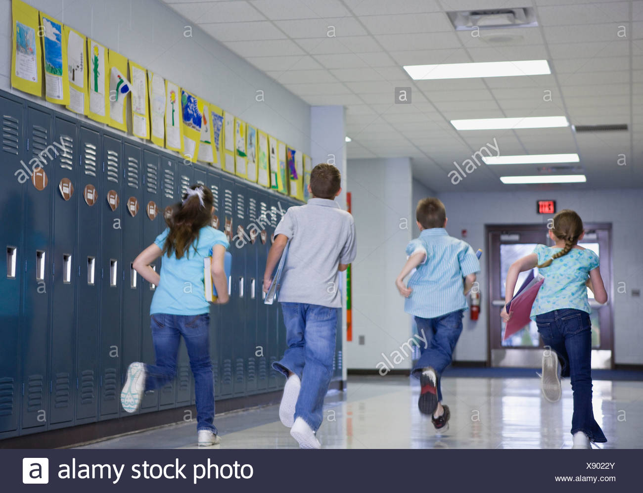 USA, Illinois, Metamora, Rear view of children (8-9, 10-11) running through school corridor - Stock Image