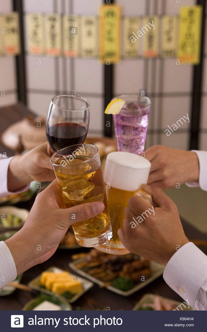 Four People Toasting with Each Other With Various Drinks at Izakaya Stock Photo