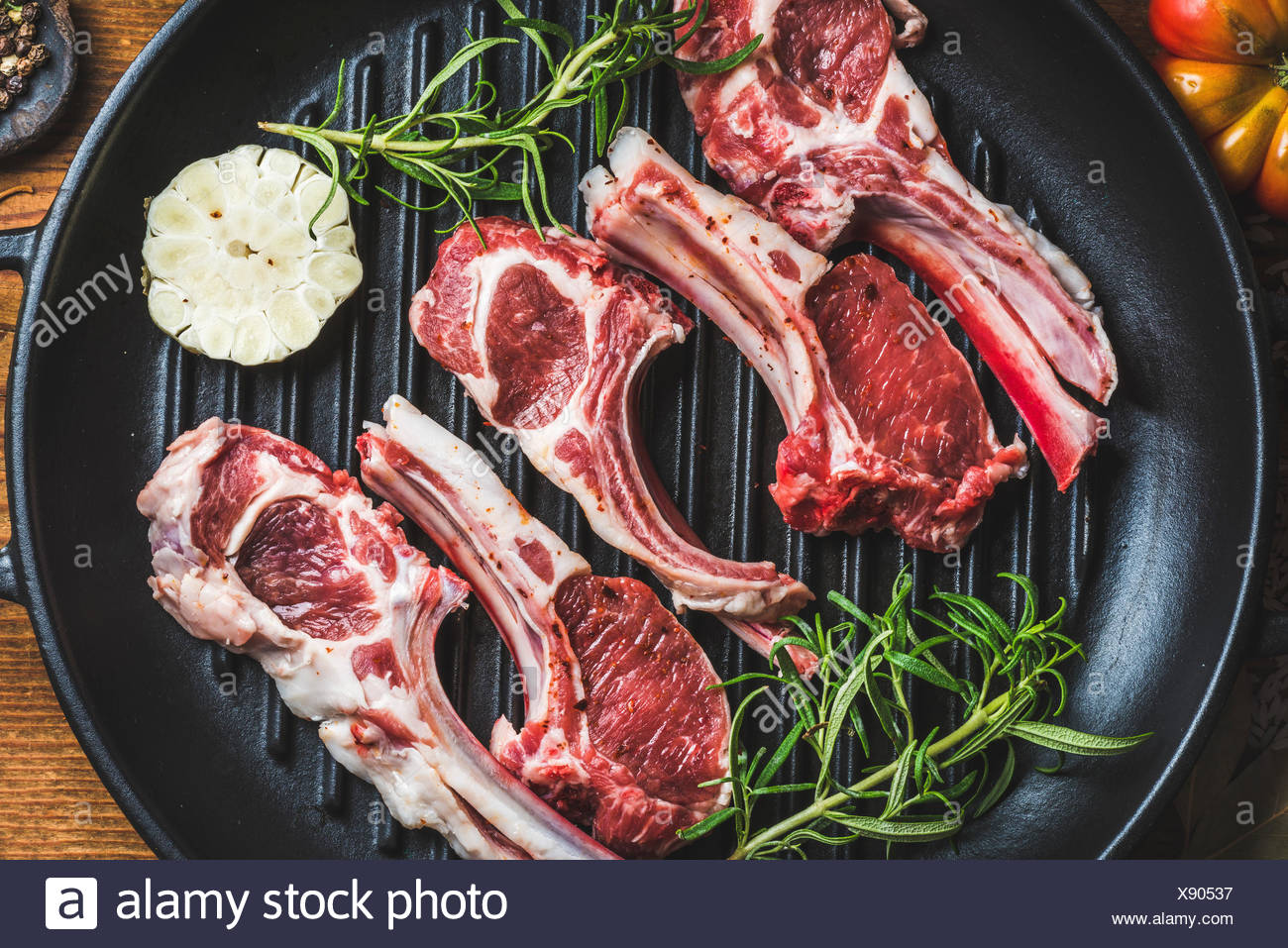 Raw uncooked lamb meat chops with rosemary and garlic in black iron grilling pan, top view, horizontal composition - Stock Image