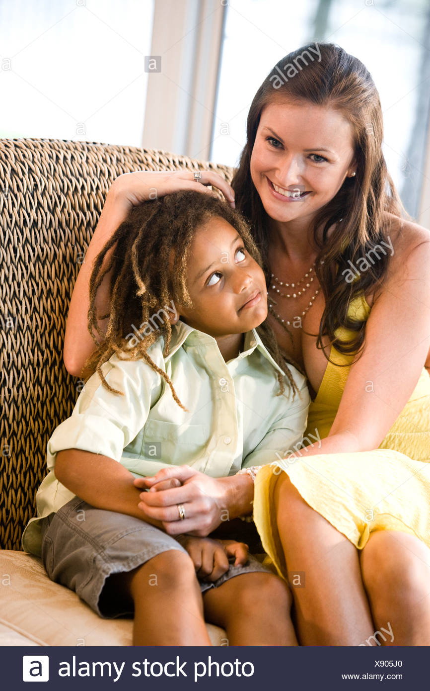 Mother and mixed race son sitting together on couch - Stock Image