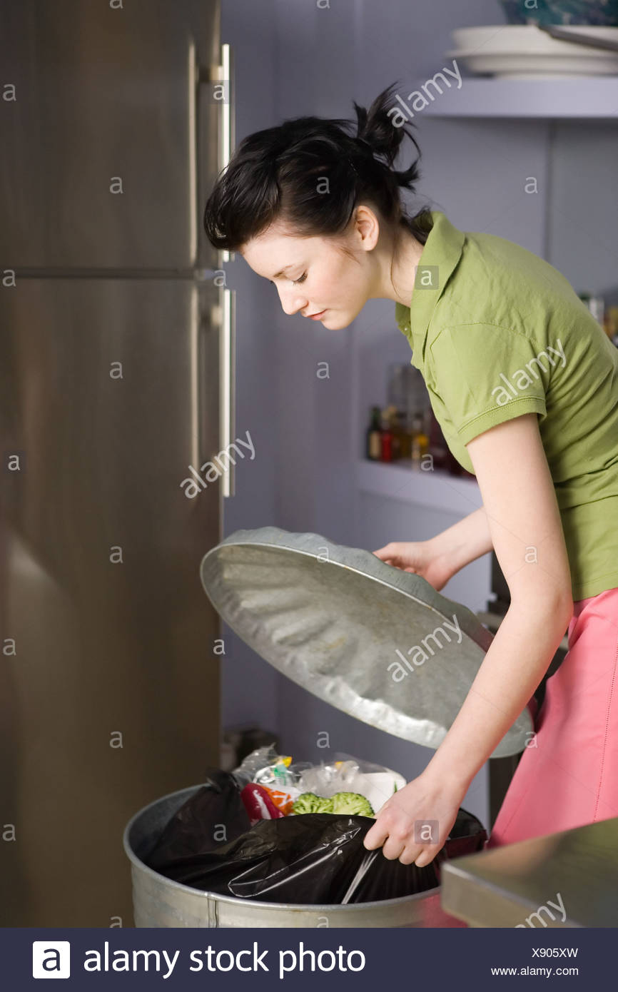 Woman pulling out rubbish bag from bin - Stock Image