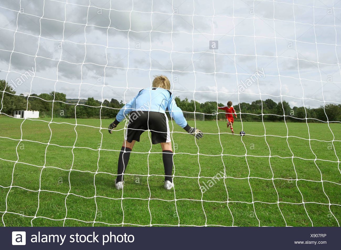 Footballer shooting at goalkeeper - Stock Image