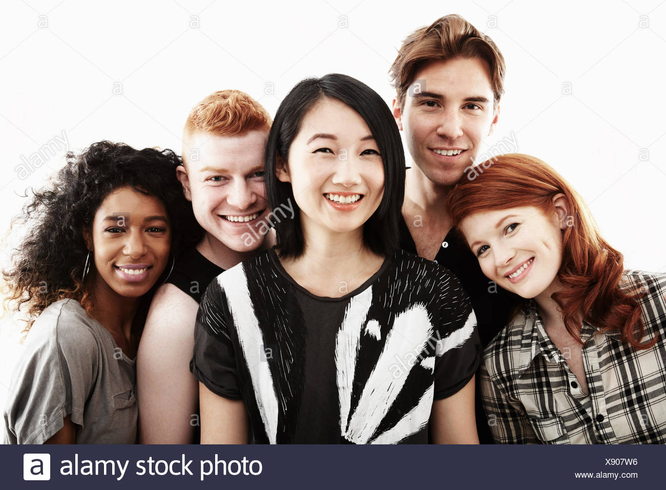 Studio portrait of five young adults smiling - Stock Image