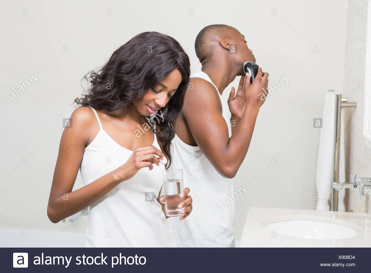 Beautiful woman putting pill in to a glass of water - Stock Image
