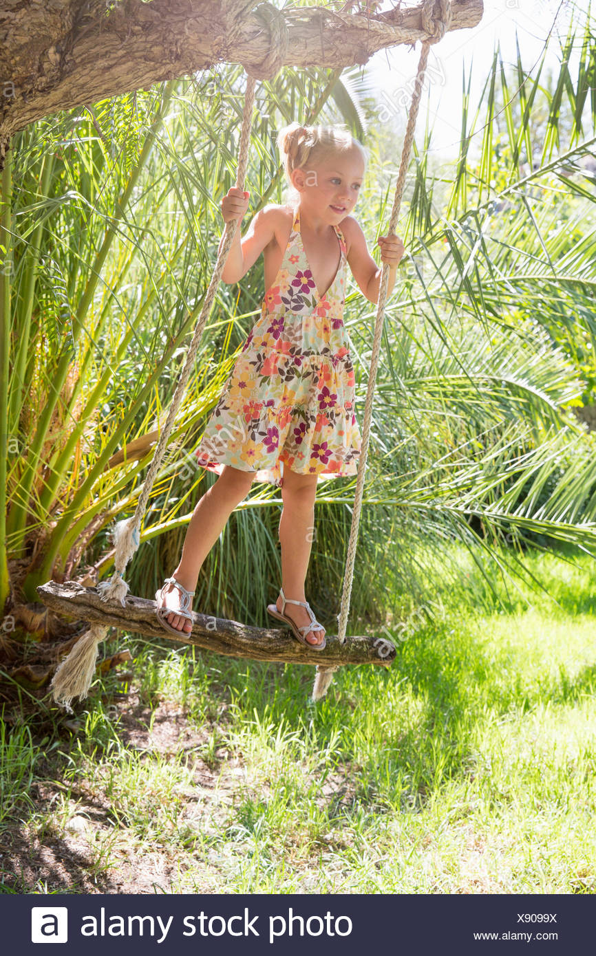 Girl standing swinging on tree swing in garden - Stock Image