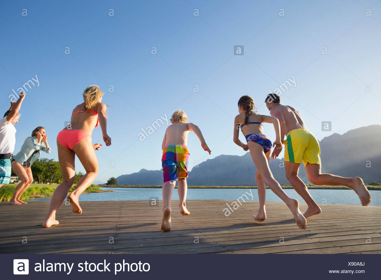 Multi generation family running to jump into lake from a jetty - Stock Image