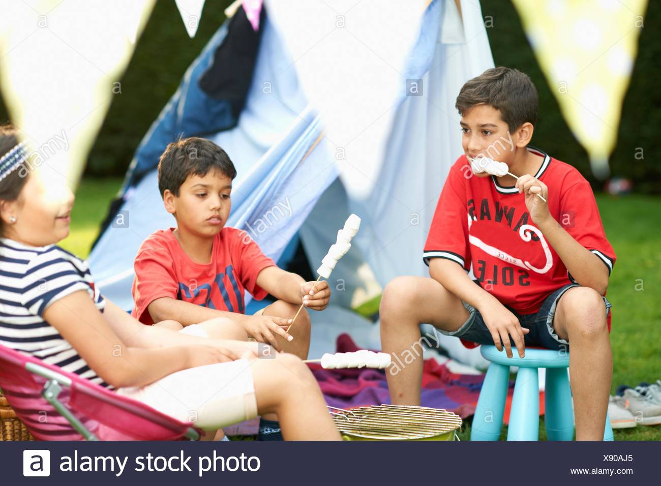 Girl and brothers eating toasted marshmallows in front of homemade tent in garden - Stock Image