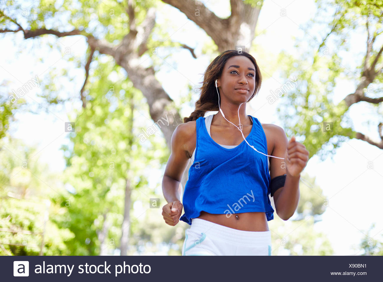 Young female runner running in park - Stock Image