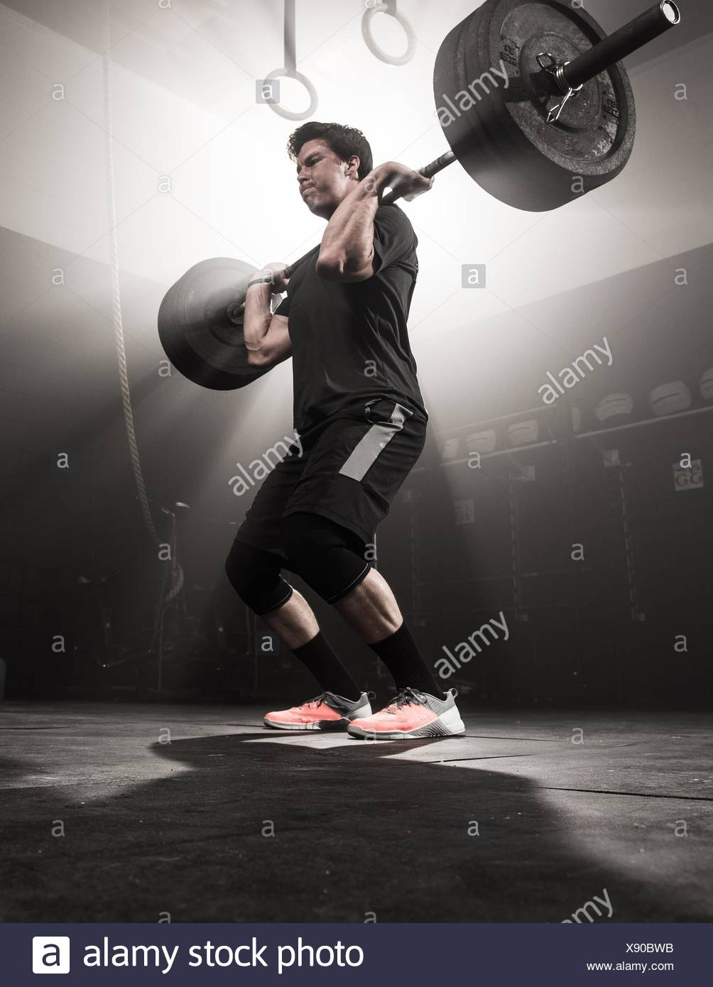 Young man lifting barbell - Stock Image