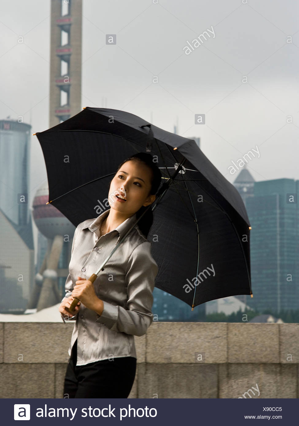 Young woman under an umbrella. - Stock Image