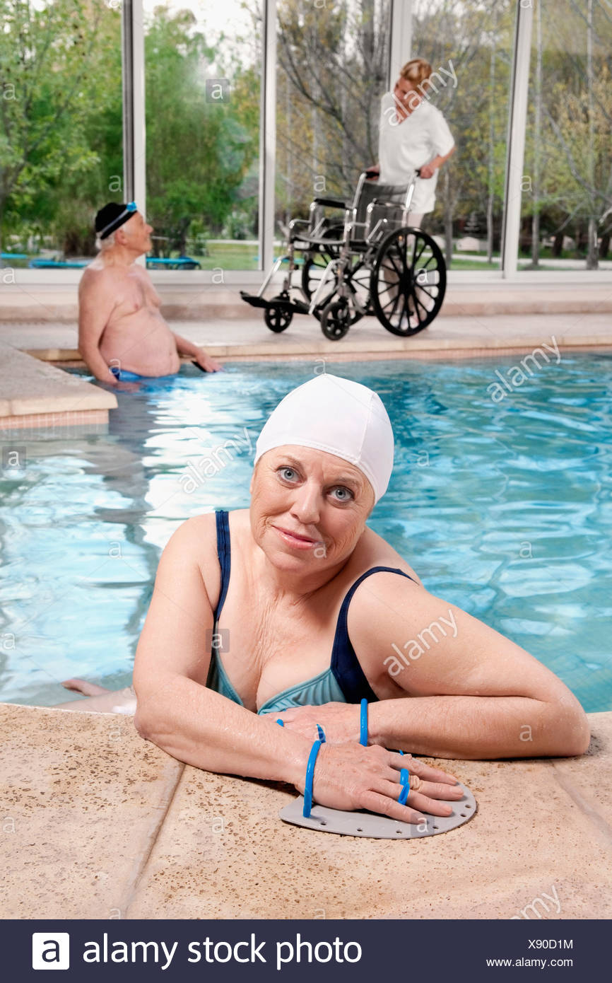 Woman wearing swim paddles in a swimming pool - Stock Image