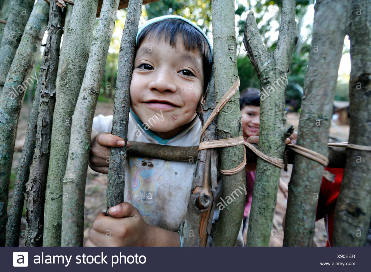 Cheeky boy, 6, looking through a gap in a fence, in the community of Mbya-Guarani Indians, Campito, Caaguazú Department - Stock Image