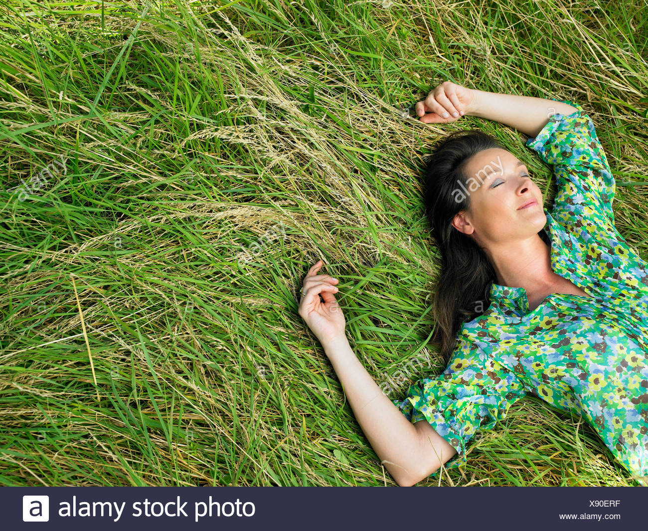 Woman laying down in a field Stock Photo - Alamy