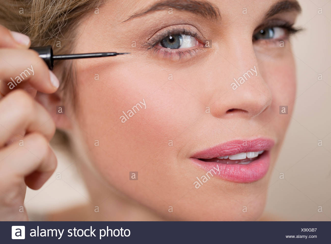 2bed84527 A young woman applying liquid eye liner, close up - Stock Image