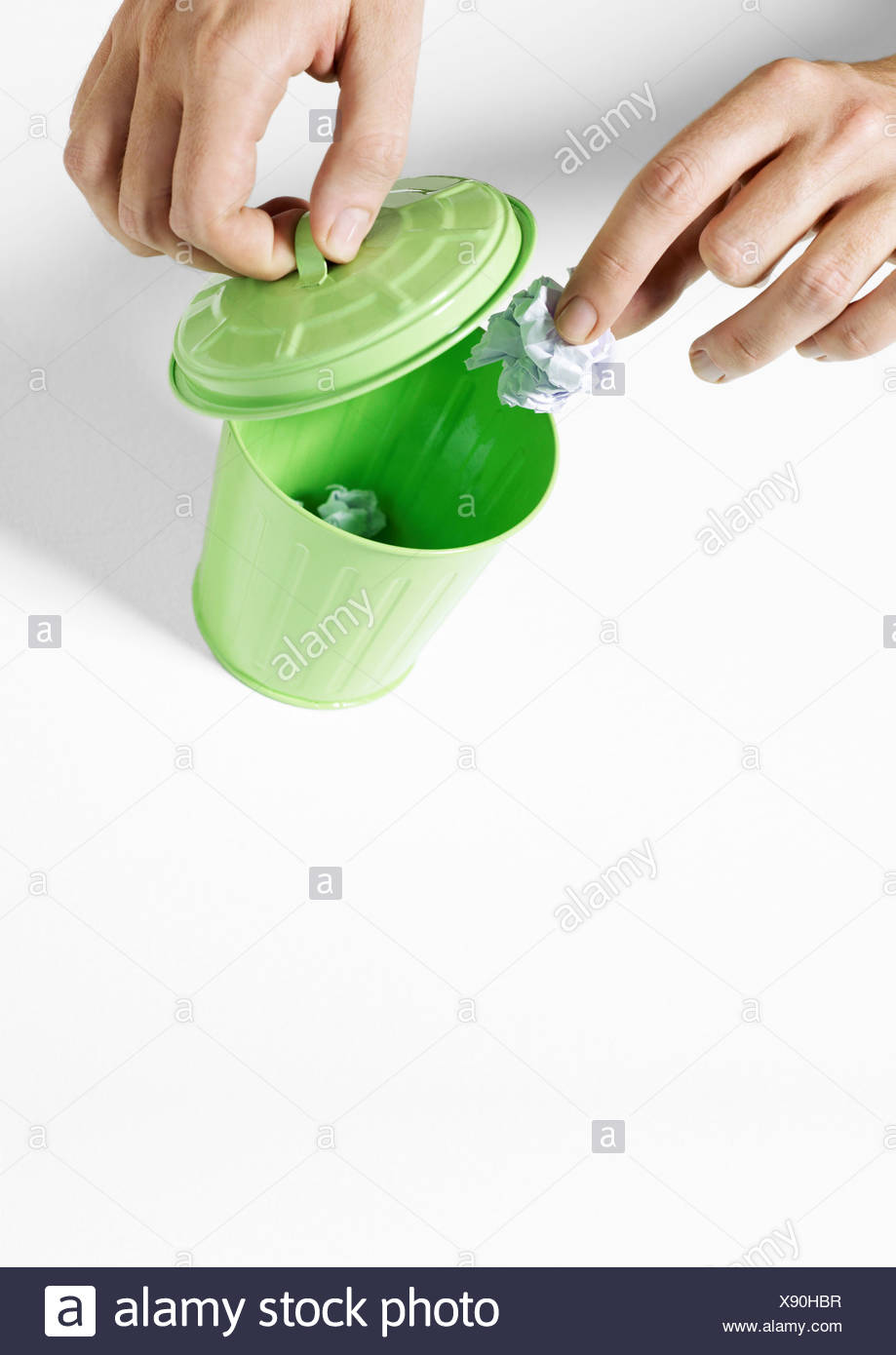 Hands putting trash in tiny trash can - Stock Image