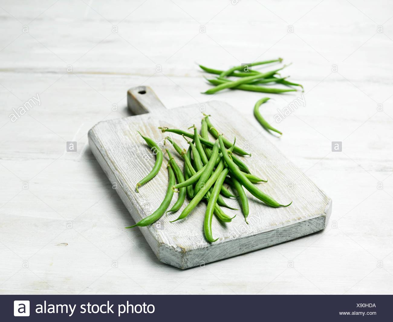 Extra fine green bean on wooden chopping board - Stock Image