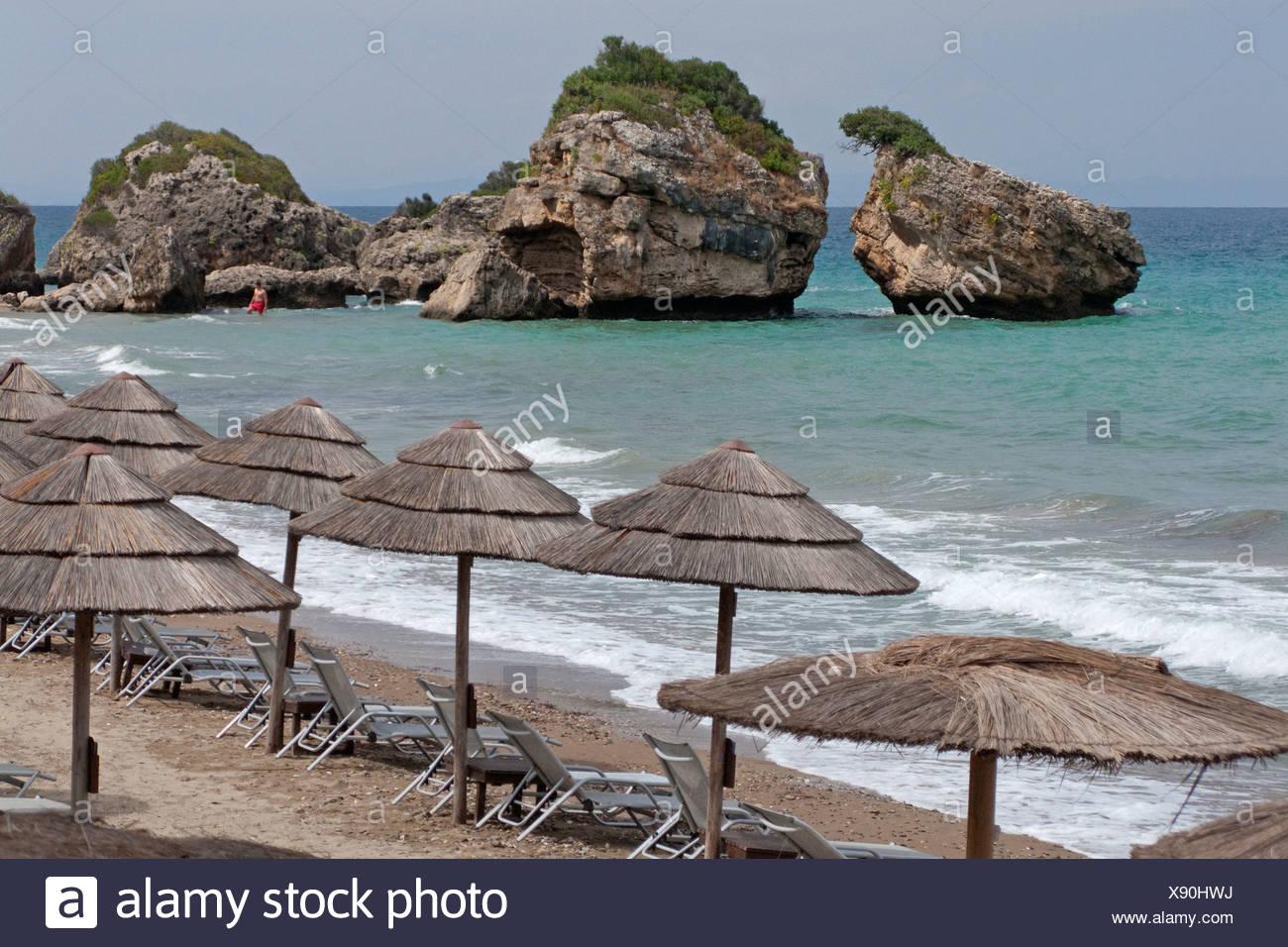 Sunshades and sun loungers on the beach of Porto Zoro, Zakynthos island, Greece, Europe - Stock Image