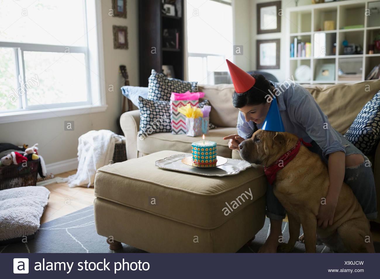 Woman and dog celebrating birthday with cake - Stock Image