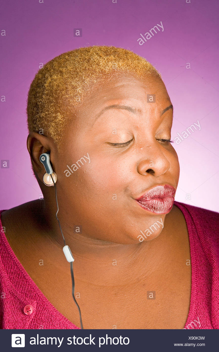 Young woman listening to headphones - Stock Image