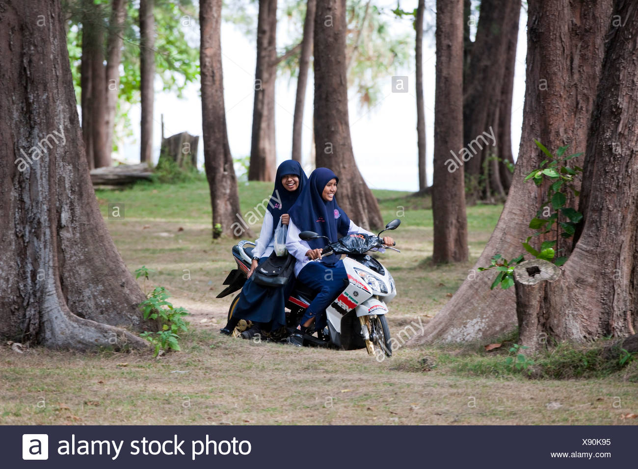 Two young Muslim women on a scooter, Nai Yang, Phuket Island, Southern Thailand, Thailand, Southeast Asia - Stock Image