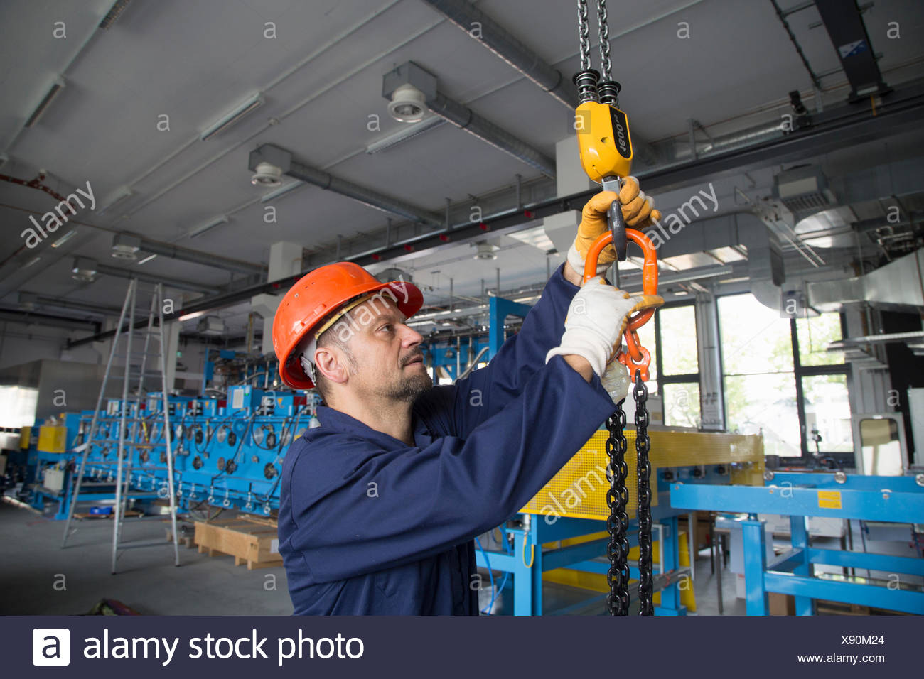 Worker adjusting chain hoist in industrial plant Stock Photo